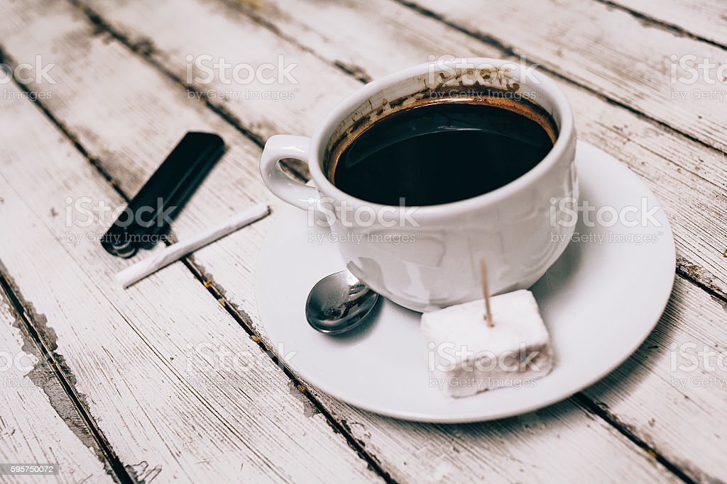 Cup of coffee with cigarette on the wooden table stock photo