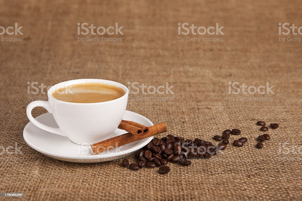 Cup of coffee with coffee beans on burlap cloth royalty-free stock photo