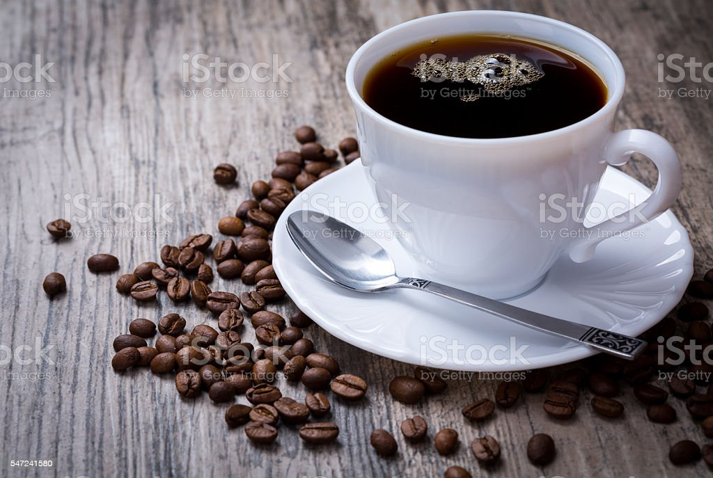 Cup of coffee with coffee beans on wooden background. stock photo