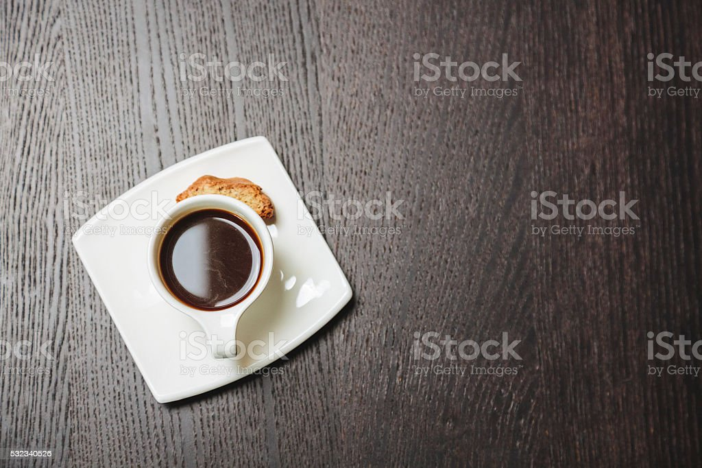 Cup of coffee with cookie on a black wooden table. stock photo