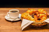 cup of coffee with croissant and a cake basket in