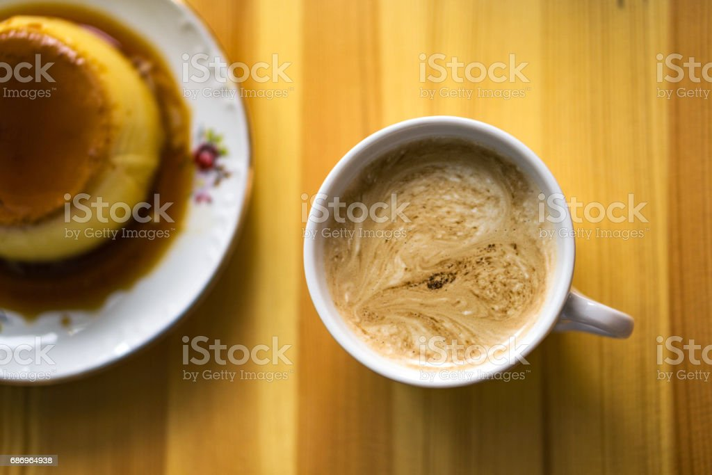 Cup of coffee with discreet heart in its cream and blurred caramel cream on the side stock photo