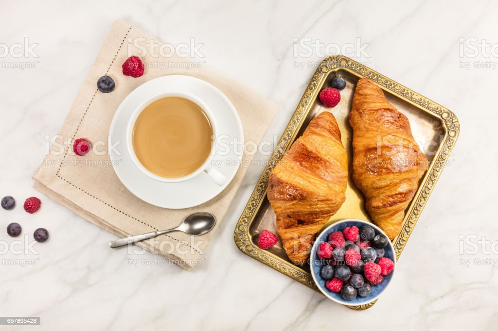 Cup of coffee with fresh raspberries, blueberries, and croissant stock photo