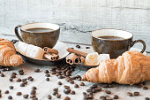 Cup of coffee with grains, croissant on wooden background