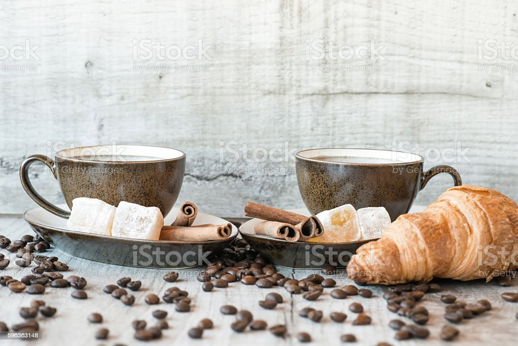 Cup of coffee with grains, croissant on wooden background stock photo