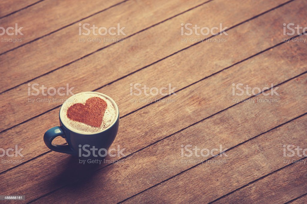 Cup of coffee with heart shape on a wooden table. stock photo