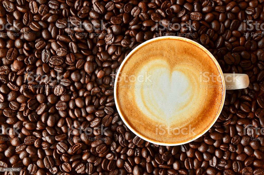 Cup of coffee with heart shape on coffee bean background stock photo
