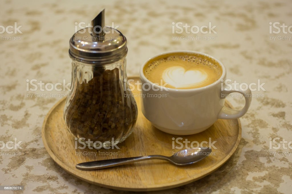 cup of coffee with leaf pattern in a white cup on wooden background