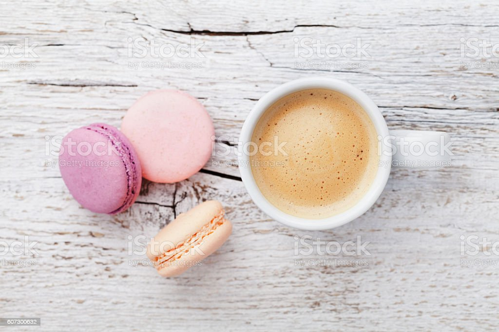 Cup of coffee with macaron on wooden table, flat lay stock photo