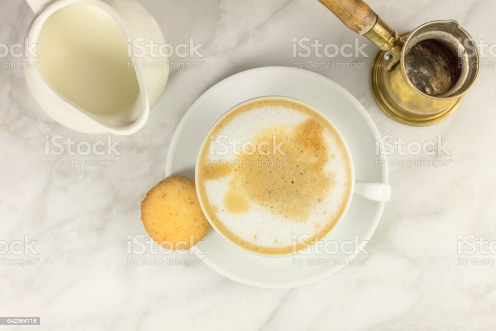 Cup of coffee with milk jar, butter cookie, and copyspace stock photo