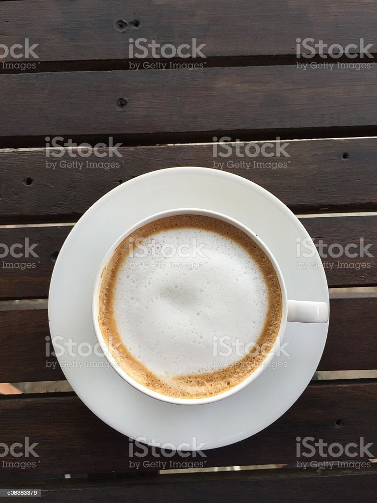 cup of coffee with milk on wood table stock photo