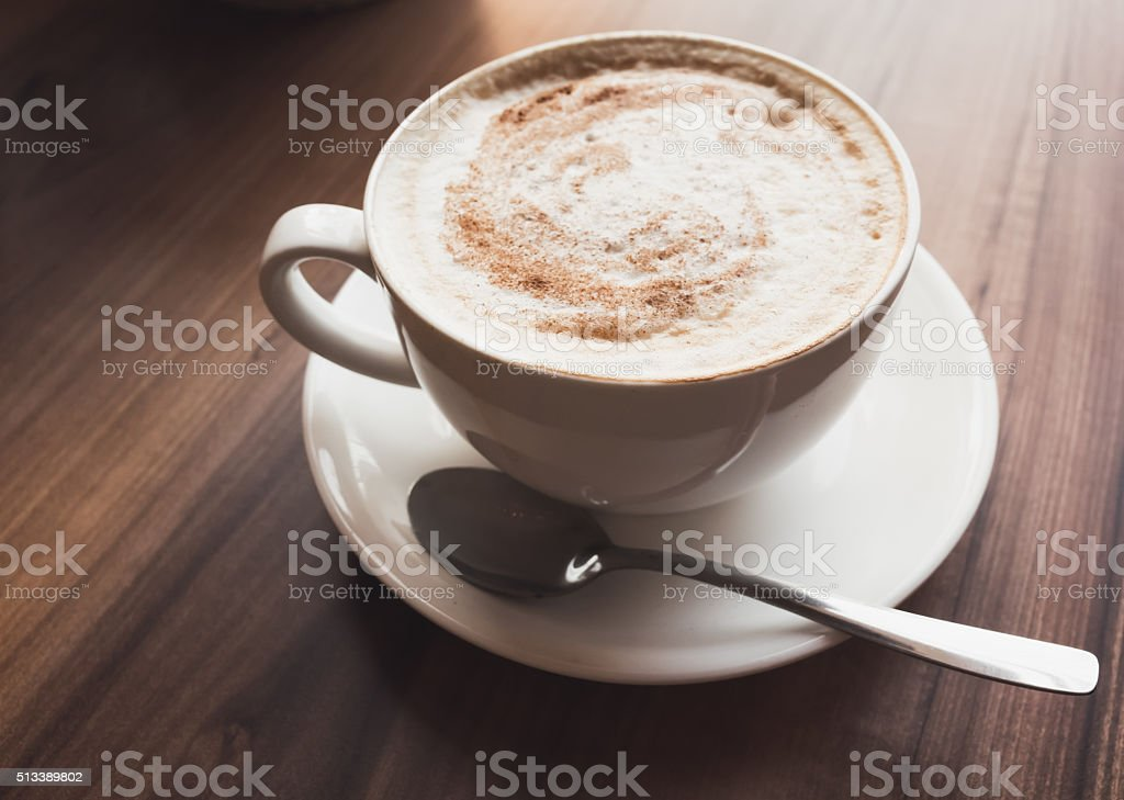 Cup of coffee with milk stands on wooden table stock photo