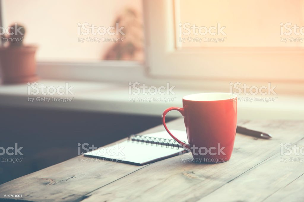A cup of coffee with notebook and pen stock photo