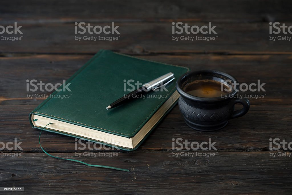 Cup of coffee with notebook on dark wooden table stock photo