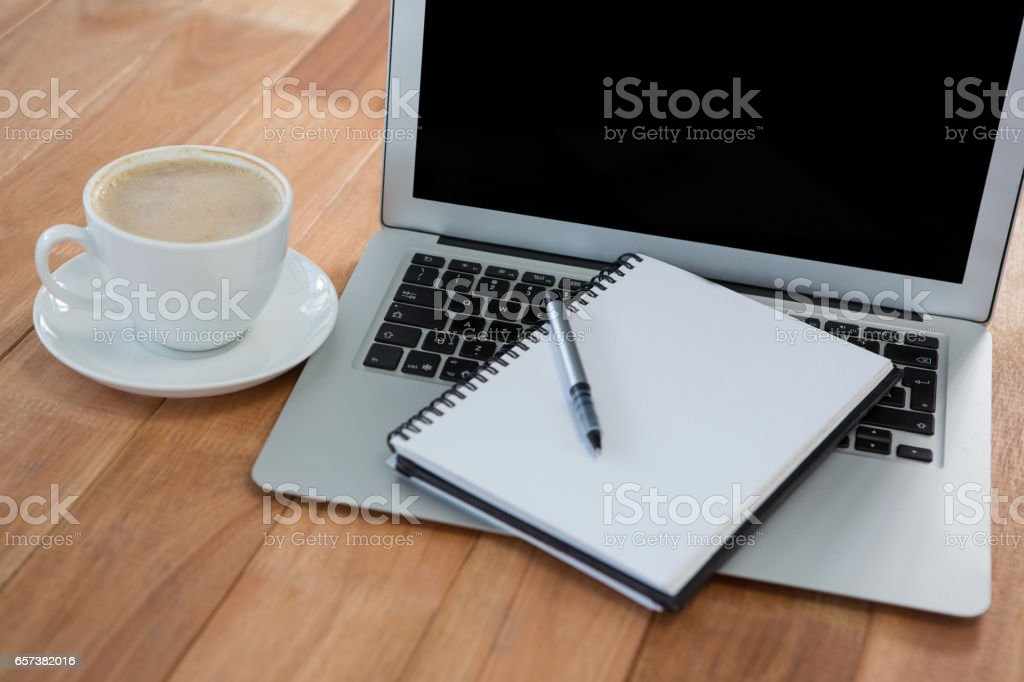 Cup of coffee with organizer and laptop stock photo