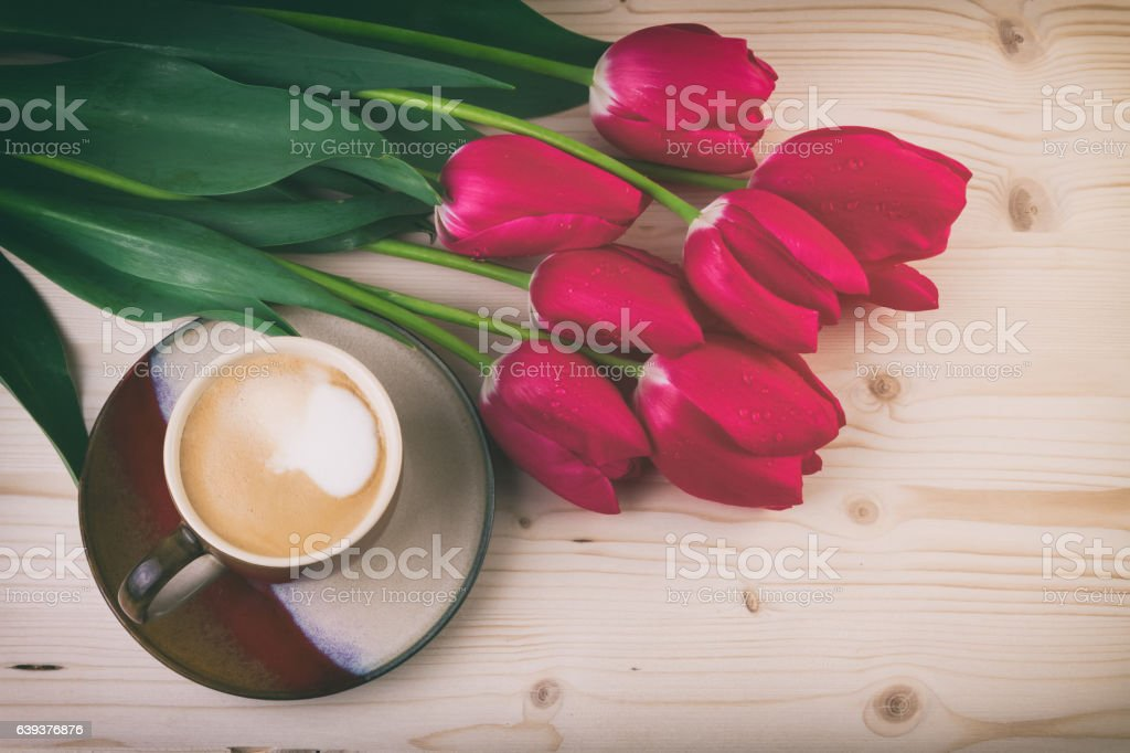 cup of coffee with red tulips on wooden table stock photo