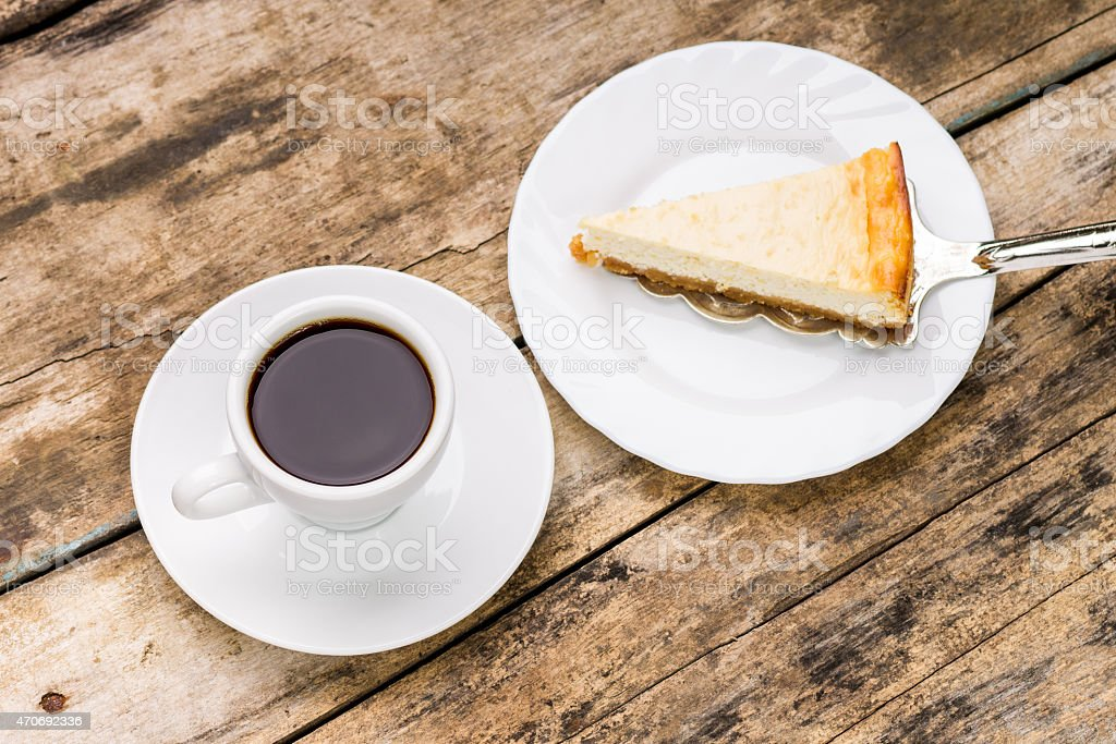 Cup of coffee with slice of cheesecake on cake server stock photo