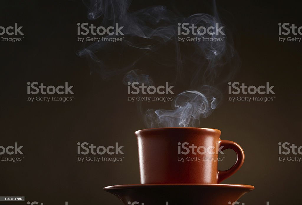 Cup of coffee with smoke over dark background royalty-free stock photo