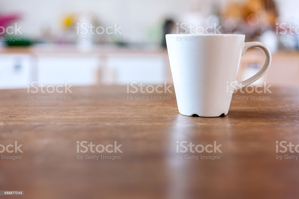 Cup of coffee with vintage kitchen defocused background. stock photo