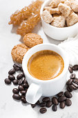 cup of espresso and sweet cookies on white table, vertical