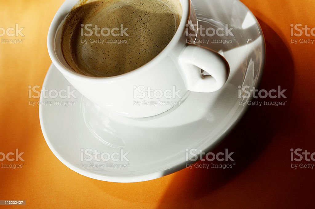 cup of espresso coffee against vibrant orange royalty-free stock photo