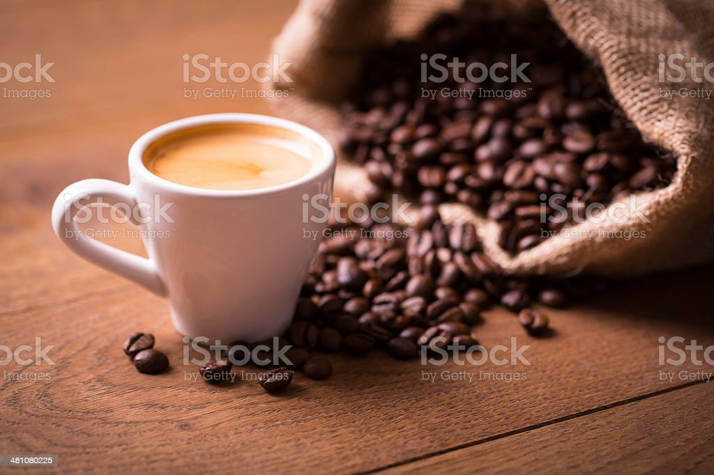 cup of espresso shot with coffee beans on wooden table stock photo