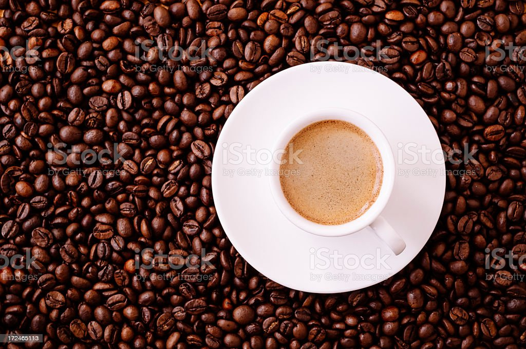 Cup of Espresso surrounded by coffee beans royalty-free stock photo