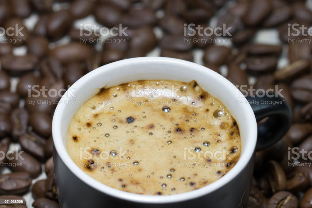 Cup of fresh cofee on background with roasted cofee beans stock photo