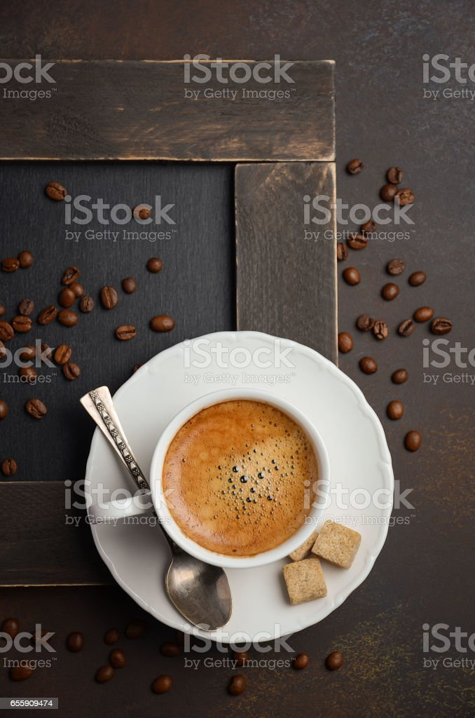 Cup of fresh coffee with coffee beans on dark background stock photo