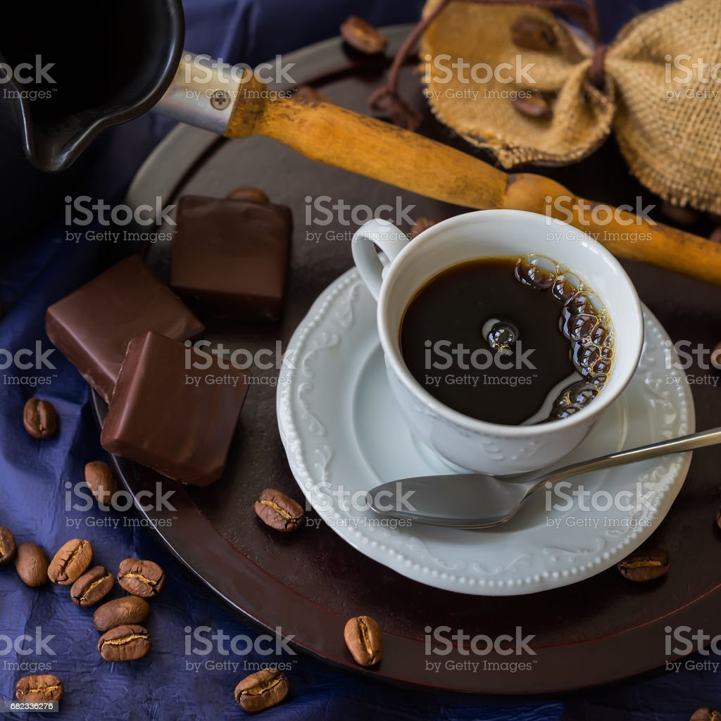 Cup of fresh hot coffee In the morning, coffee beans, turk, bitter chocolate, wooden background. Low key image, vintage style. Concept of morning exercise, good mood stock photo