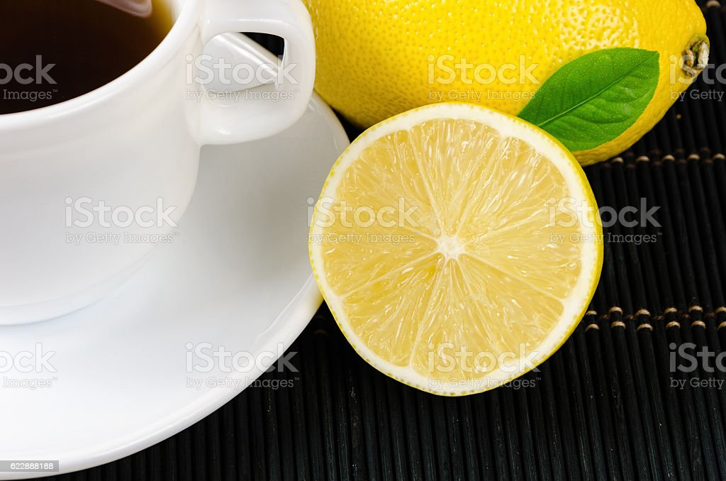 cup of fresh tea with lemon on rustic wood background stock photo