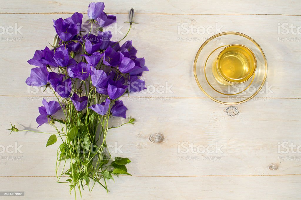 Cup of green tea and a bouquet of blue bells stock photo