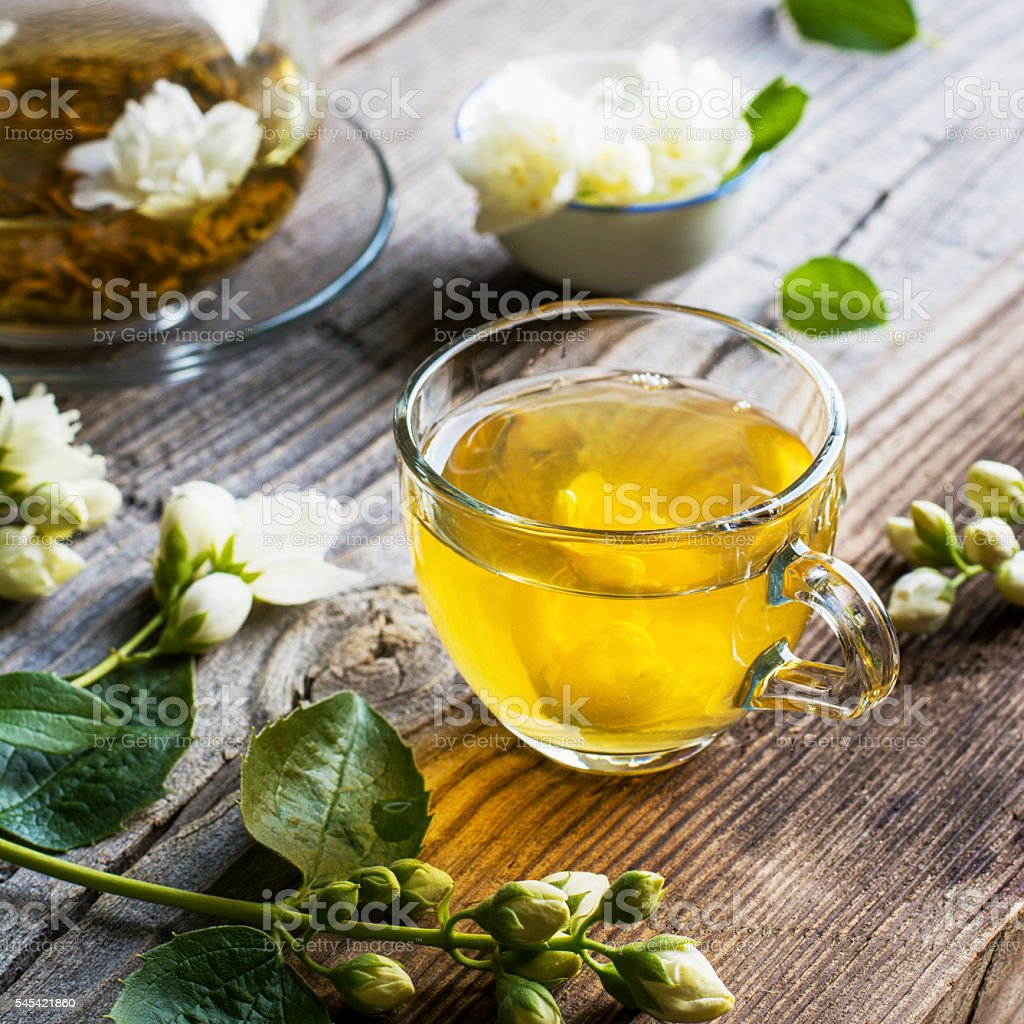 cup of green tea infused with jasmine on a gray stock photo
