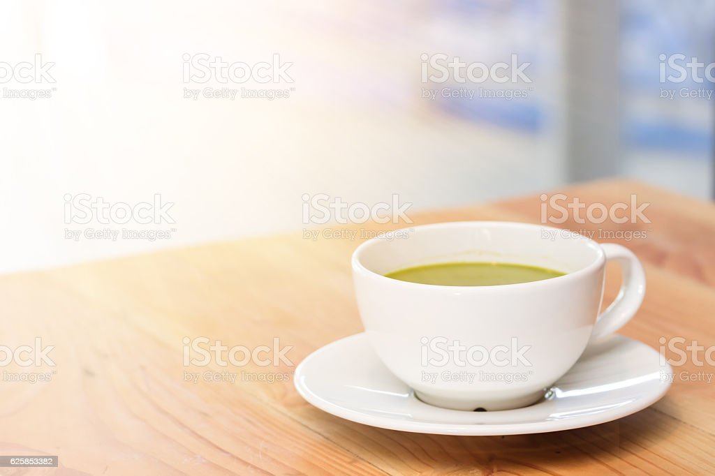 A cup of green tea on wooden table stock photo