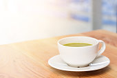 A cup of green tea on wooden table