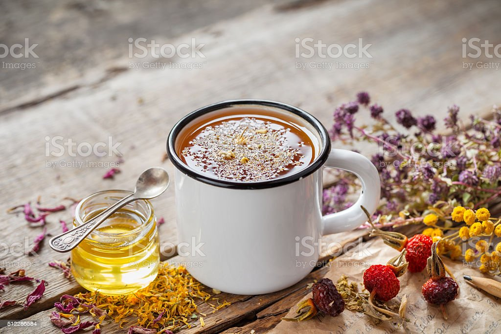 Cup of healthy daisy tea, honey and healing herbs stock photo