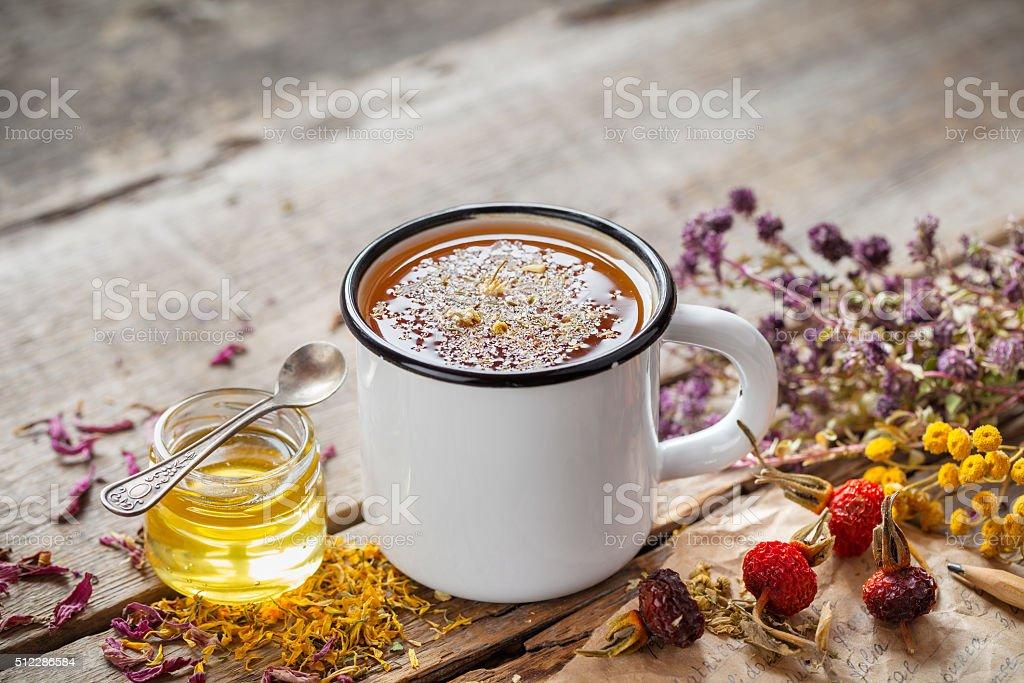 Cup of healthy daisy tea, honey and healing herbs stock photo