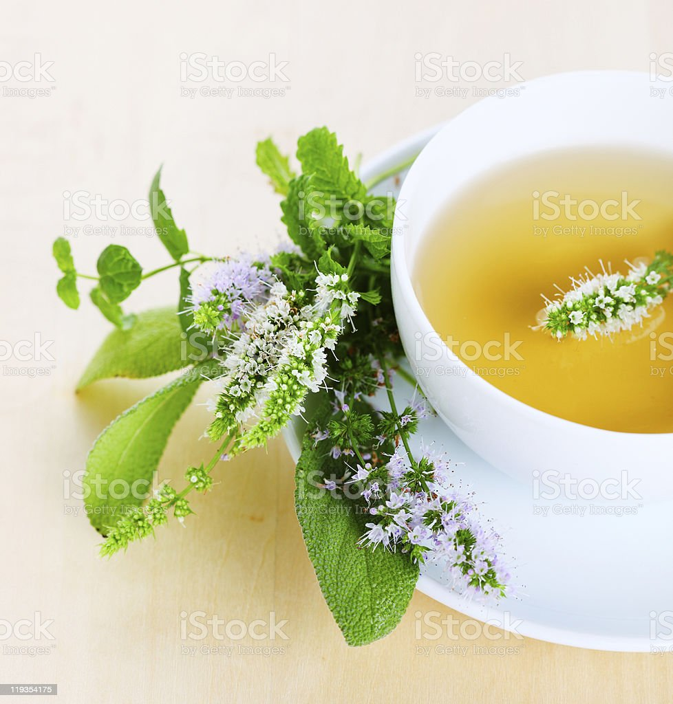 cup of herbal tea and edible flowers stock photo