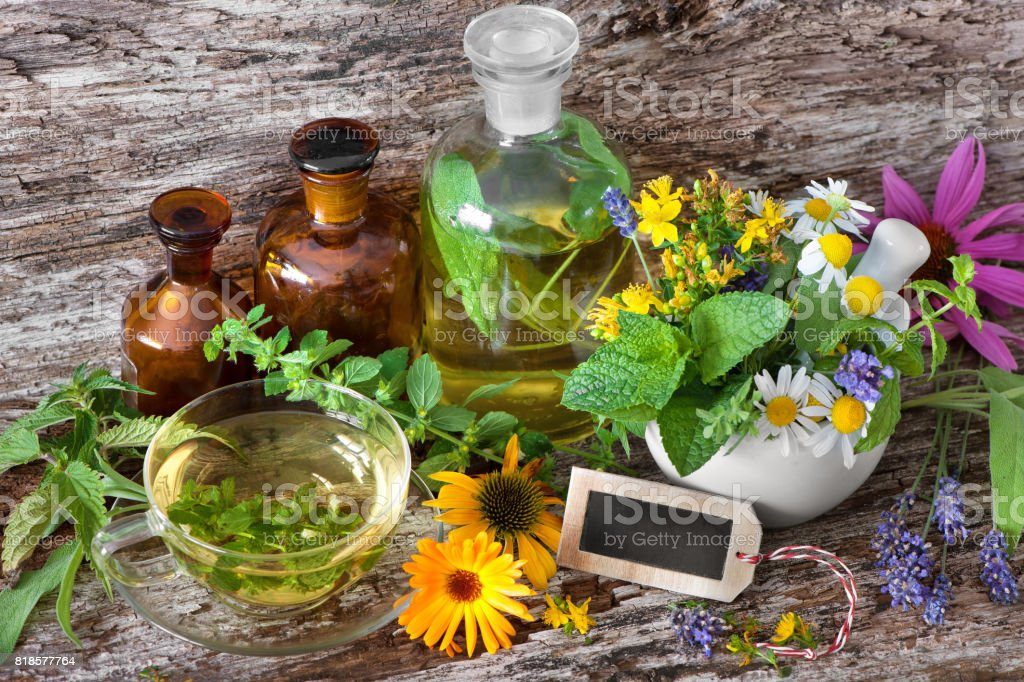 Cup of herbal tea with medicinal bottles and healing herbs in mortar stock photo