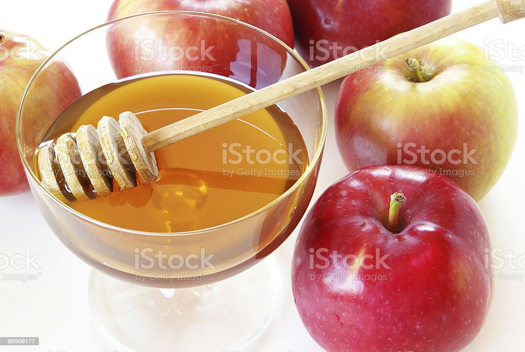 Cup of honey with stirrer and whole apples for Rosh Hashana stock photo