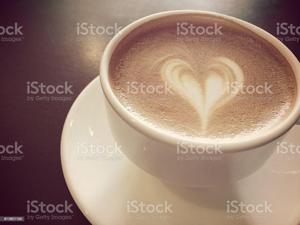 cup of hot cappuccino over heart foam on the  table royalty-free stock photo
