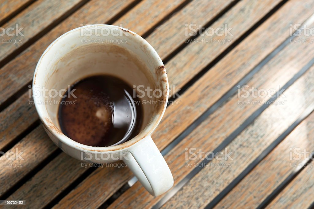 Cup of hot chocolate left on wooden table stock photo