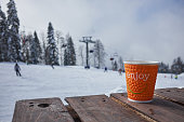 Cup of hot chocolate on wooden table over winter ski