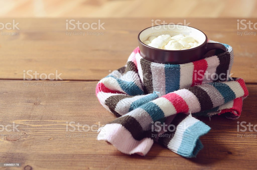 cup of hot chocolate with marshmallows wrapped scarf stock photo