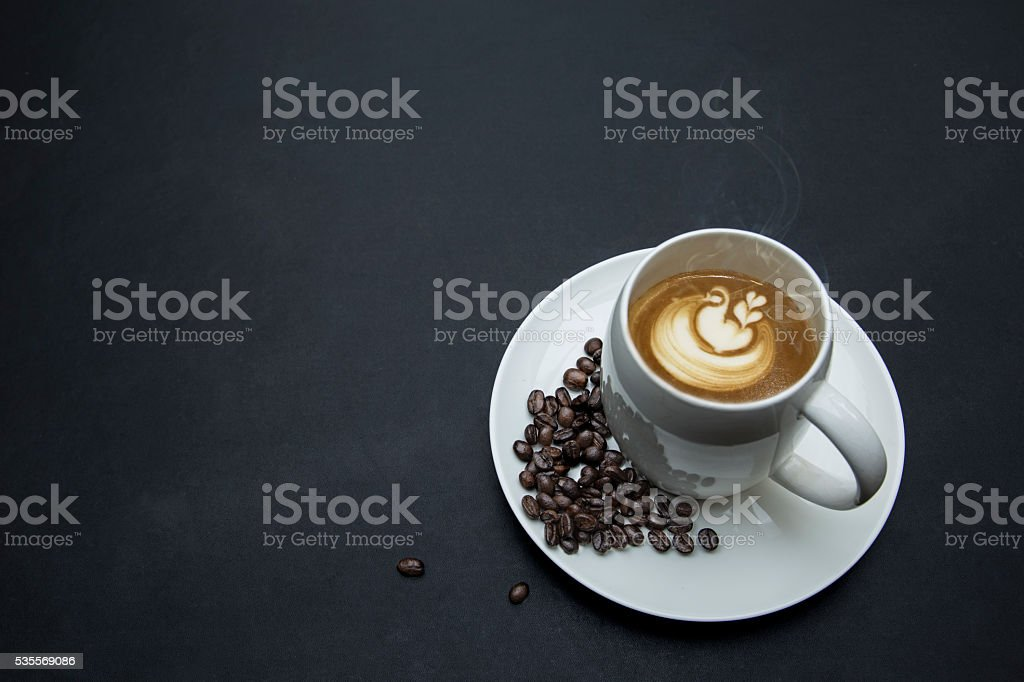 cup of hot coffee, coffee bean decoration on leather background royalty-free stock photo