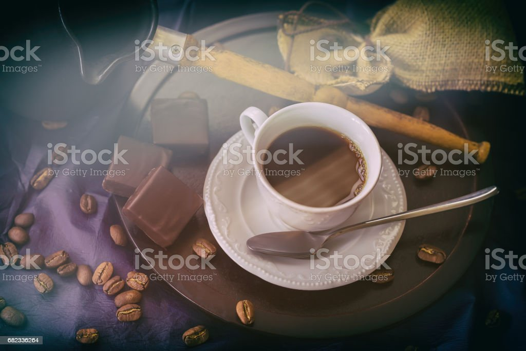 Cup of hot coffee in morning sunshine, coffee beans, turk, dark chocolate, wooden background. Low key image, vintage style. Concept of hormone of happiness, good mood stock photo