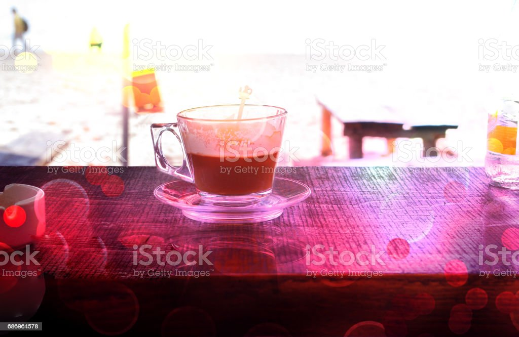 Cup of hot coffee ona a table on the beach. stock photo