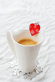 Cup of hot coffee with decorative heart and engagement ring
