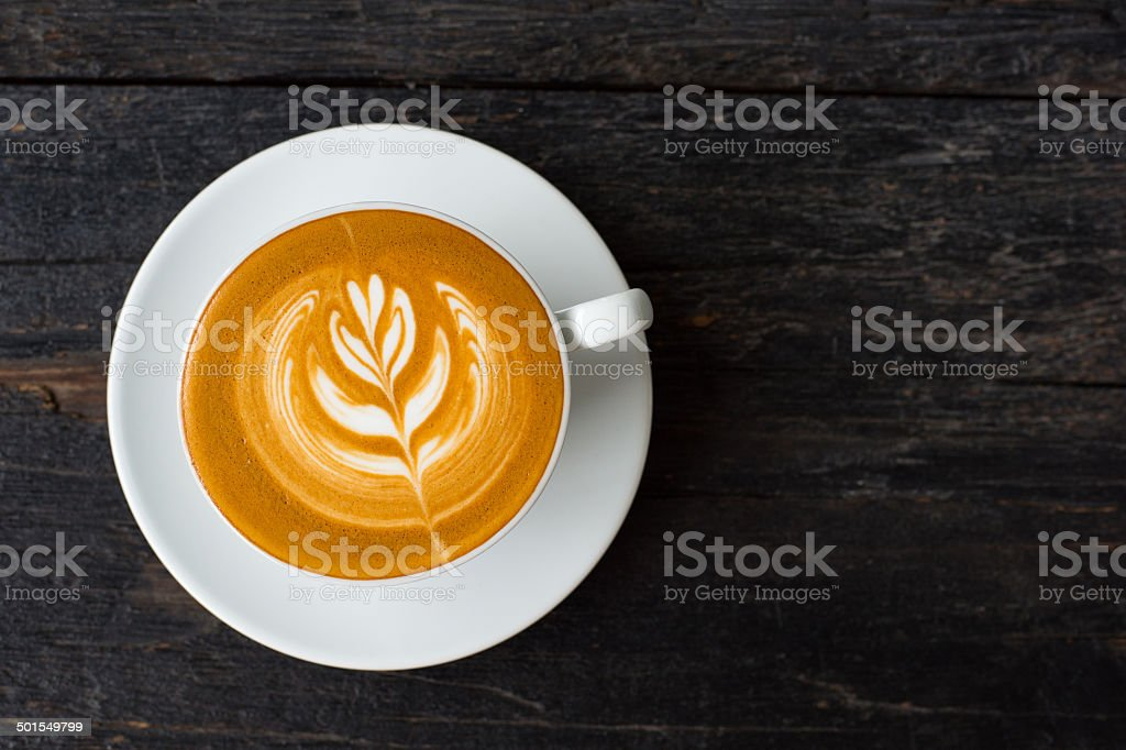Cup of hot latte art coffee on wooden table. stock photo