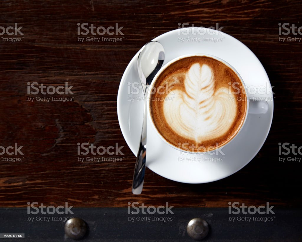 A Cup of hot latte art coffee on wooden table stock photo